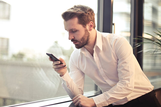 Businessman watching SAM Booking App on his mobile phone